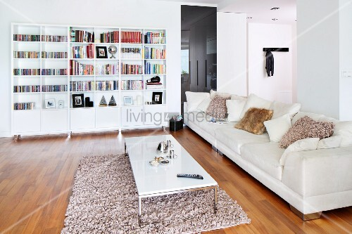 Long, pale sofa with fur scatter cushions, coffee table on flokati-style rug and shelving units with base cabinets against wall