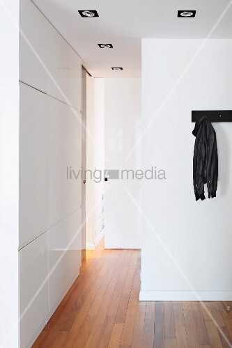 Hallway with white fitted cupboards and wooden floor; black jacket hanging from coat rack on wall