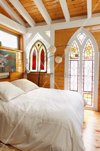 Bedroom with stained glass window and wooden beam ceiling; Taos; New Mexico; USA