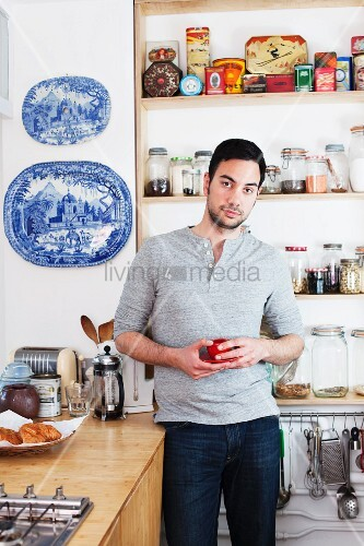 Man standing in kitchen holding coffee cup
