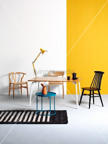 Simple wooden table with white metal frame against white and yellow wall