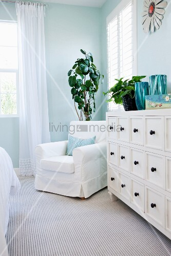 Arm chair by drawers in bedroom