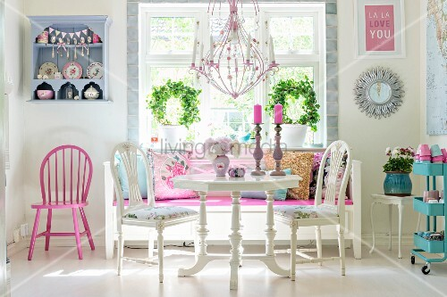 Pink chandelier above white dining set and bench below window
