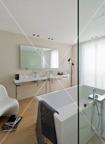 Free-standing white bathtub behind glass screen opposite twin washstands below large mirror in minimalist designer bathroom