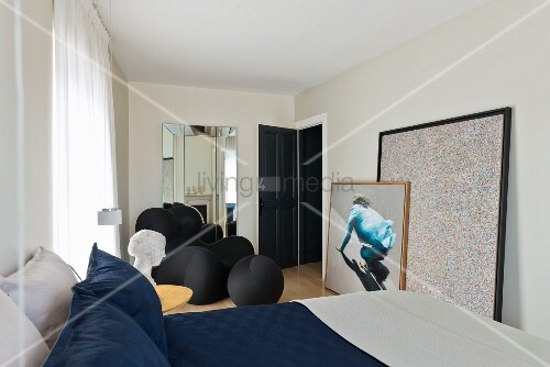 Double bed in modern bedroom with sculptural armchair by Gaetano Pesce and large, modern artworks leaning against wall