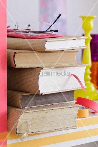 Bücherstapel im Regal mit selbstgemachten Buchumschlägen aus Packpapier