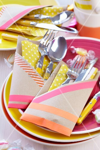 Hand-crafted cutlery pockets made from brown paper stuck together with washi tape