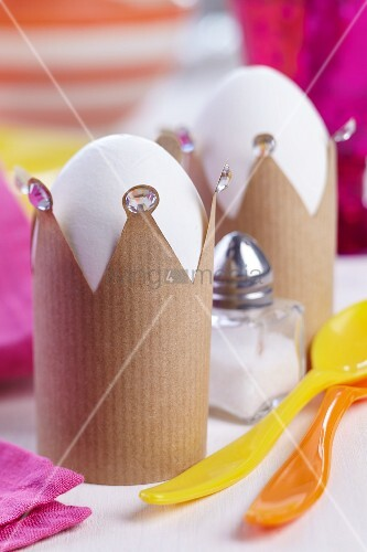 Crown-shaped eggcups made from brown paper decorated with rhinestones