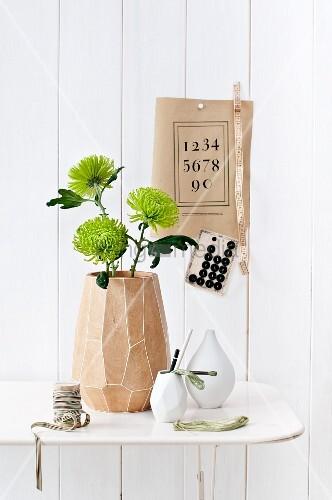 Three chrysanthemum 'Anastasia' flowers in mango-wood vase on white metal table; vintage items decorating wall