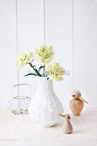 Green carnation in modern white vase and small bird ornaments