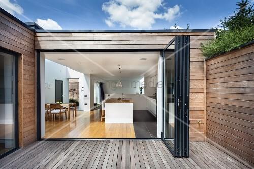 holzterrasse eines zeitgen ssischen wohnhauses mit holzverschalung blick durch offene faltt r. Black Bedroom Furniture Sets. Home Design Ideas