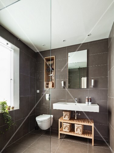 Grey-tiled bathroom with shelves in niche above toilet next to sink and wooden shelves; glass partition in foreground