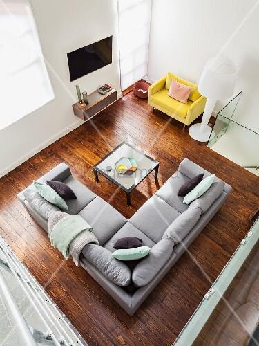 blick von oben auf graues ecksofa und couchtish auf dunklem dielenboden in der ecke gelber. Black Bedroom Furniture Sets. Home Design Ideas