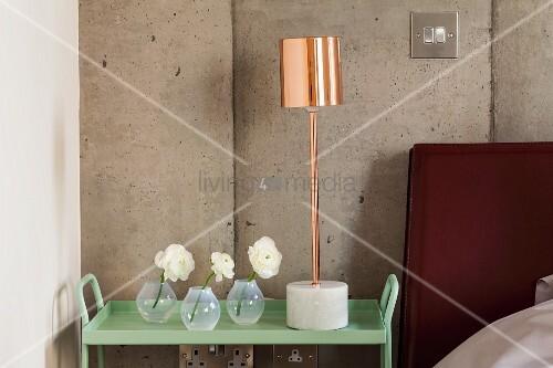 Glasvasen und Tischleuchte mit kupferfarbenem Schirm auf Beistelltisch in Pastellgrün lackiert