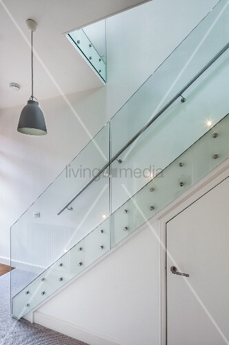 Modern staircase with glass balustrade; storage space with door below