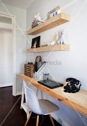 Untreated wooden shelves above wooden desk in home office with vintage telephone and classic chair