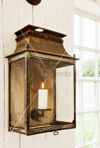 Vintage, metal candle sconce with lit candle behind glass screen hung on wooden wall