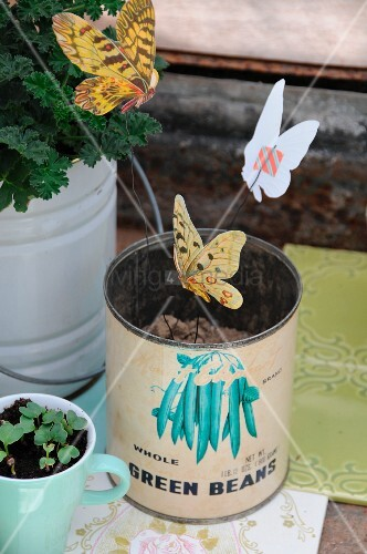 Paper butterflies attached to wire using washi tape and stuck in vintage food tin