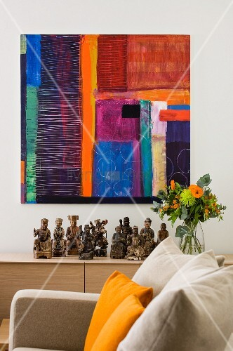 View over couch to modern artwork on white wall above collection of wooden figurines and bouquet on sideboard