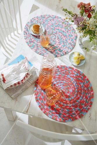 Erfrischungsgetränke auf selbstgehäkelten Tischsets aus Melange Garn auf weißem Tisch