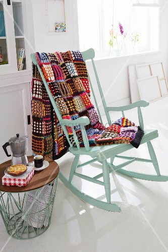 A colourful, crocheted patchwork blanket on a rocking chair next to a side table with an espresso jug