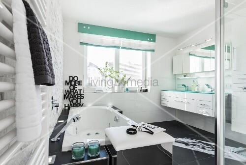 Modernes, schwarz-weisses Badezimmer mit Whirlwanne, davor ...