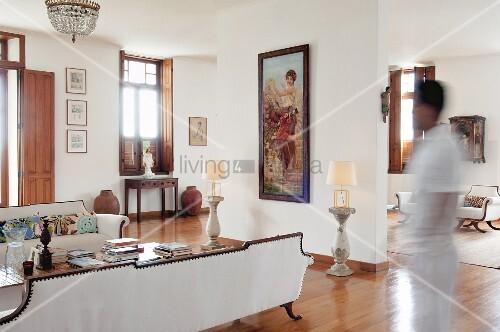 Elegantes Foyer mit weisser Sofagarnitur, vor Raumteiler hochformatiges Bild zwischen Tischleuchten auf Steinstelen