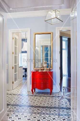 Foyer with patterned tiled floor, and red, postmodern chest of drawers against wall between open interior doors