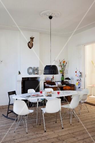 Schwarze Pendelleuchte über weißem, ovalem Esstisch mit Schalenstühlen; Kamin und Homeoffice im Hintergrund