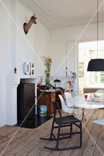 Rehkopf-Trophäe und Buchstabendeko an Kaminwand in Esszimmer mit Klassikerstühlen und traditionellem Sekretär im Hintergrund