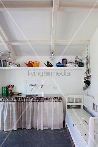 Giesskannen Und Küchenutensilien Auf Bord Unter Einer Dachschräge, Darunter  Der Spülenschrank Mit Vorhang Und Seitlich Eine Alte Truhenbank