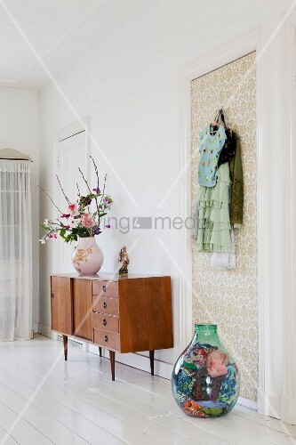 Vase of flowers on 50s, retro sideboard and demijohn full of scarves on floor below coat hooks on wallpapered door