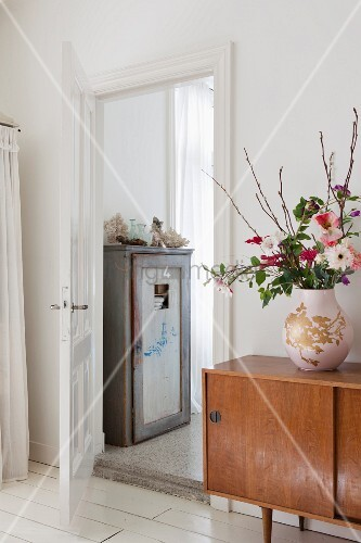 Bulbous vase of flowers on retro sideboard next to open door showing old wooden cupboard in ensuite bathroom