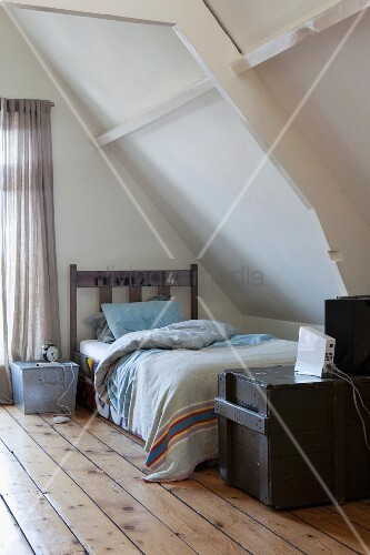Teenager's attic bedroom with old, black-painted shipping crate at foot of wooden bed