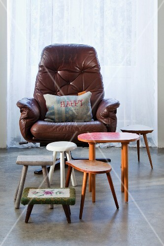 Retro collection of various stools and side tables in front of cushion with 'Happy' motif on leather swivel chair