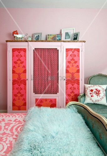 Old wardrobe with panels decorated with floral wallpaper and curtains; antique bed with turquoise faux fur blanket