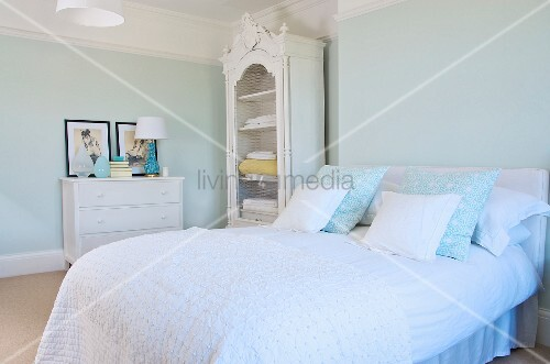 French bed with scatter cushions and white bedspread and white-painted, carved, rustic linen cupboard in pastel bedroom in period apartment