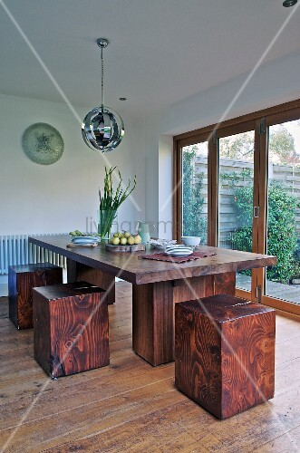 Custom dining table and cubic, red wood stools next to terrace doors