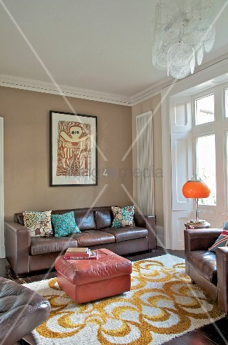 Pink, leather ottoman on patterned rug and brown leather sofa and armchair in traditional interior