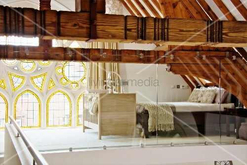 Bedroom on gallery behind glass screen with exposed wooden roof structure and Neogothic rose window with stained glass elements