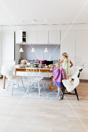 Children at set dining table with black and white kitchen chairs with sheepskin blankets in front of white fitted cupboards