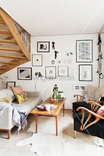 Wooden coffee table between armchair and pale, fifties-style couch, gallery of frames pictures on wall and detail of staircase to one side
