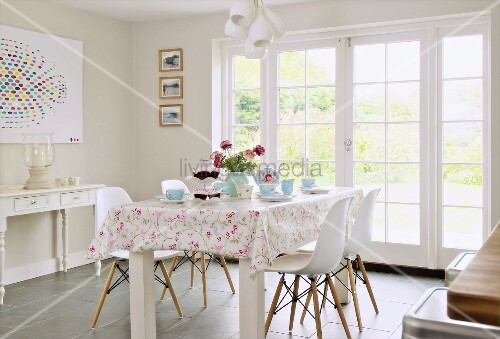 Rustic dining area with white classic chairs in front of terrace doors