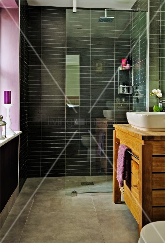 Modern bathroom, glass partition screening shower area with black wall tiles and solid-wood washstand