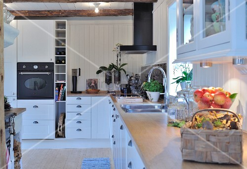 Modern, L-shaped, fitted kitchen with white cupboards and white wood-clad walls