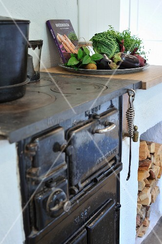 Old, cast iron cooker and plate of vegetables on top of masonry firewood store