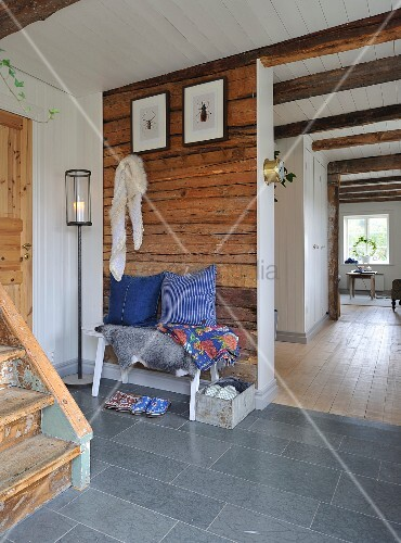 Entrance hall in old, Swedish wooden house with white-clad sections of wall and ceiling