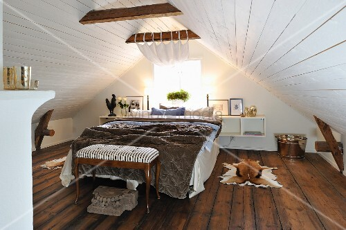 Double bed and antique bedroom bench under white-clad gable ceiling in attic room with dark wooden floor
