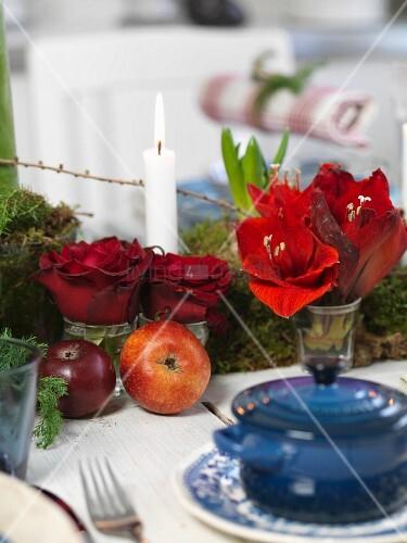 Blaues Töpfchen mit Deckel vor weihnachtlichem Tischdeko, rote Amarylisblüten und Rosen in Vase