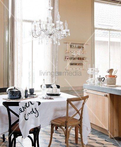 Chairs in dark and pale wood around table with white tablecloth and modern kitchen counter in kitchen-dining room